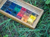 Benutzte wasserbasierte Farbfarbe in den Behältern auf dem grünen Hintergrundabschluß oben Lizenzfreie Stockbilder