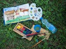 Benutzte wasserbasierte Farbfarbe in den Behältern mit einem benutzten Malerpinsel auf dem grünen Hintergrund Stockfoto