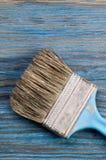 Benutzter Pinsel auf blauem hölzernem Brett mit Platz für Text Stockbild