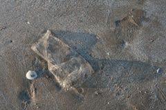 Benutzter Plastiktascheabfall auf Sandstrand Stockfotografie