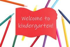 Benvenuto al messaggio di asilo sul segno di legno rosso con le matite colorate dell'acquerello fotografia stock libera da diritti