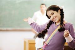 Benvenuto al mio banco: sorridere adorabile della scolara Fotografie Stock Libere da Diritti