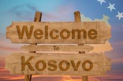 Benvenuto al segno del Kosovo su fondo di legno con la bandiera nazionale di mescolamento Immagini Stock
