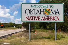 Benvenuto al segno di Oklahoma con cielo blu ed agli alberi nei precedenti immagini stock