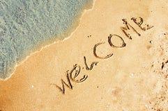 Benvenuto scritto in una spiaggia sabbiosa Fotografia Stock