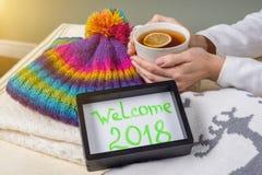Benvenuto 2018, testo nel telaio Fondo dell'abbigliamento di inverno e tazza di tè caldo con il limone Fotografie Stock Libere da Diritti