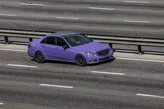 Benz de Mercedes accordant expédier bleu sur la route vide Photos stock
