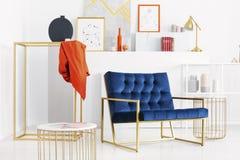 Benzine blauwe sofa in het midden van modieuze witte woonkamer met gouden toebehoren en partij van art. stock foto