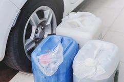 Benzine in gallons naast een auto stock fotografie