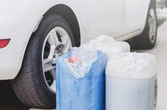 Benzine in gallons naast een auto royalty-vrije stock afbeeldingen
