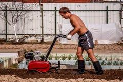 Benzinelandbouwer in actie betreffende het de landbouwperceel Stock Fotografie