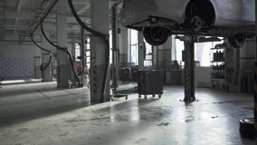 Benzinestation met machines met behoefte aan reparatie Één auto wordt opgeschort boven de vloer, is de tweede nabijgelegen stock footage