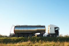 Benzinetankwagen op de weg met open cabinedeur en vrachtwagenchauffeur daarin stock foto's