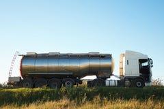Benzinetankwagen op de weg met open cabinedeur en vrachtwagenchauffeur daarin royalty-vrije stock afbeelding