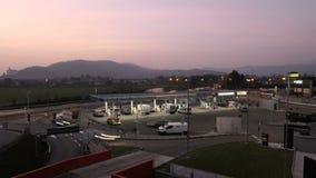 Benzynowa stacja w długim ujawnienia świetle z wiele samochód w usłudze zdjęcie wideo