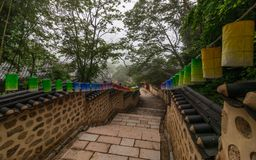 Pathway steps to Korean Buddhistic Temple Beomeosa with many lanterns to celebrate buddhas birthday on a foggy day. Located in royalty free stock photography