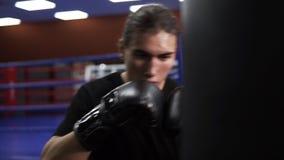 Bepaald kickboxer raakt in dozen doende peer Een boze bokser zet een stempel in een in dozen doende zak in zwarte handschoenen Tr stock videobeelden