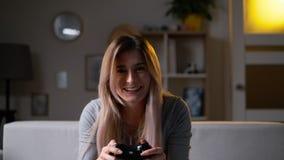 Bepaald meisje die een videospelletje thuis spelen Opgewekte gamer vrouwenzitting op een laag die, die en in videospelletjes spel stock videobeelden