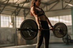 Bepaalde en sterke vrouw met zware gewichten stock foto