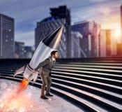 Bepaling en machtszakenman die een raket houdt Startconcept royalty-vrije stock afbeelding