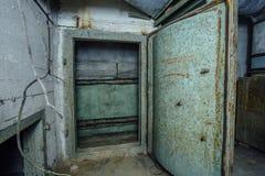 Bepansrad dörr för gammalt rostigt stål i övergiven sovjetisk militär bunker fotografering för bildbyråer