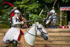 Bepansrad riddare på hästryggen som laddar i en joust Royaltyfri Foto