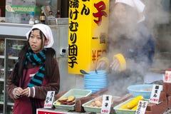Beppu, Giappone - 29 dicembre 2009: Due ragazze che cucinano alimento sul mercato di aria aperta Gli uova sode, il mais e le pata fotografia stock