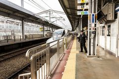 Beppu, Japão - 30 de dezembro de 2009: Estação de Beppu das chegadas do trem de bala de Shinkansen, passageiros que esperam um tr imagens de stock