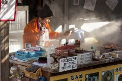 Beppu, Japão Vendedor da mulher que cozinha os ovos cozidos, alimento popular da rua em Beppu foto de stock royalty free