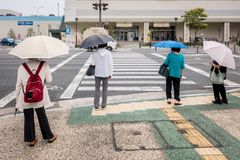 Four women with umbrellas stand in front of a pedestrian crossing stock image