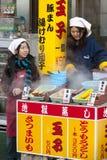 Beppu, Japon - 29 décembre 2009 : Deux jeunes filles faisant cuire la nourriture sur le marché d'extérieur Les oeufs à la coque,  images libres de droits