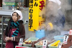 Beppu Japonia, Grudzień, - 29, 2009: Dwa młodej dziewczyny gotuje jedzenie na outdoors rynku Gotowani jajka, kukurudza i grule, s zdjęcie stock