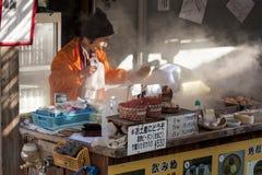 Beppu, Japonia Kobieta sprzedawcy kucharstwo gotował się jajka, popularny uliczny jedzenie w Beppu zdjęcie royalty free