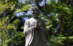 Monument of a Praying, buddhist monk. Green Vegetation in the background stock photos