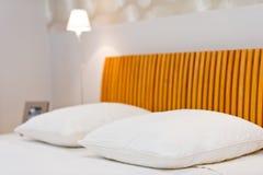 Bequeme Kissen auf dem Bett mit Lampe im Hintergrund Lizenzfreies Stockfoto