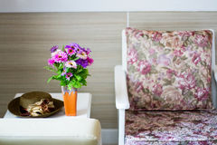 Bequemer Lehnsessel mit Kissen und Decke gegen weiße Wand Stockbilder
