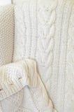Bequemer Stuhl mit Weiche strickte Decke und Kissen auf ihm Stockfoto