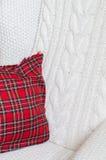 Bequemer Stuhl mit Weiche strickte Decke und Kissen auf ihm Stockbild