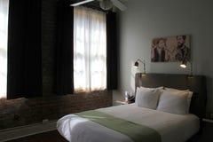 Bequemes Bett, mit Backsteinmauern und kühlen Akzenten, alte kein 77 Hotel u. Chandlery, New Orleans, 2016 Stockfotos