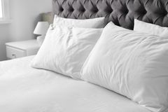 Bequemes Bett mit weißem Leinen und Kissen lizenzfreies stockfoto