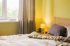 Bequemes Bett mit weichem Kissen im Rauminnenraum lizenzfreies stockbild