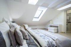 Bequemes enormes Bett im hellen Schlafzimmer Stockbilder
