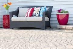 Bequemes modernes Sofa auf einem Patio im Freien stockfotos