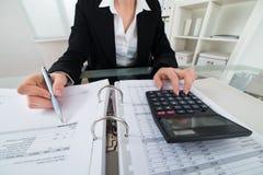 Beräknande faktura för affärskvinna royaltyfri foto