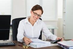 Beräknande skatt för affärskvinna på skrivbordet fotografering för bildbyråer