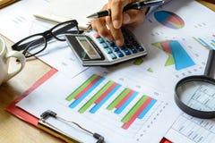 Beräknar Graph den finansiella redovisningen för skrivbordkontorsaffär, analy Arkivbilder