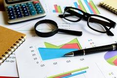 Beräknar Graph den finansiella redovisningen för skrivbordkontorsaffär, analy Arkivfoto
