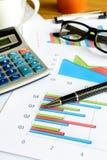 Beräknar Graph den finansiella redovisningen för skrivbordkontorsaffär, analy Arkivbild