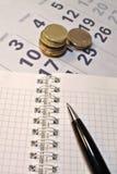 Beräkning av kostnadsbegrepp Penna, kalender, anteckningsbok och mynt Arkivfoto