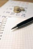 Beräkning av kostnadsbegrepp Penna, kalender, anteckningsbok och mynt Royaltyfri Foto